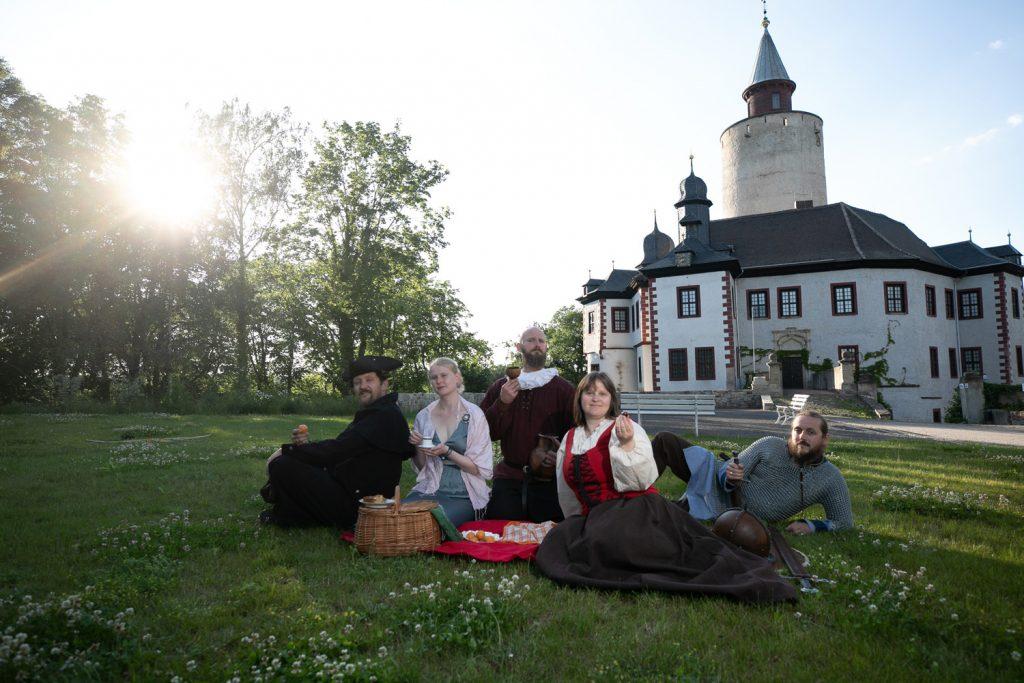 Fünf Leute aus verschiedenen Zeiten beim gemeinsamen Picknick vor der Burg Posterstein. Mit Genuss durch die Jahrhunderte - in dieser Führung geht es ums Essen (Foto: Ronny Ristok, Gefolgschaft zu Posterstein)